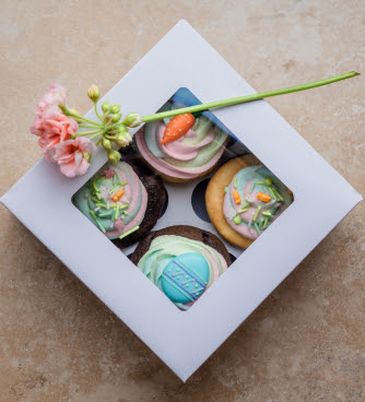 Box of cupcakes with flower on top